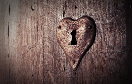 A lock in the shape of a heart rusts away on an old wooden door.