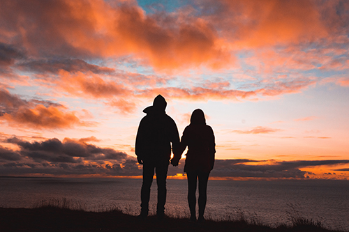 A man and a woman stand next to each other, holding hands and looking at the ocean while the sun sets