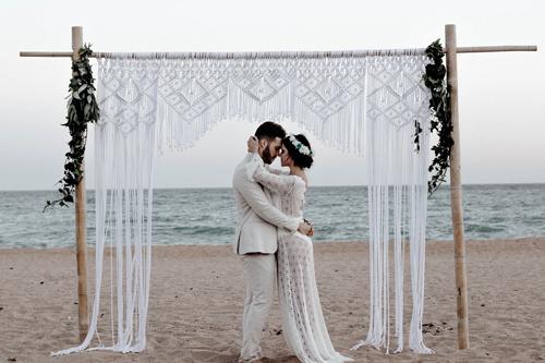 A couple on a beach with a macrame backdrop and non-traditional wedding attire.