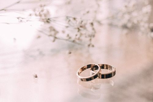A photo of two rings placed on a reflective surface with branches in the background
