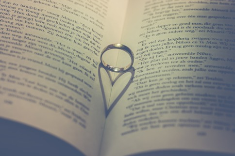 A wedding ring balanced between pages of a book casting a heart-shaped shadow