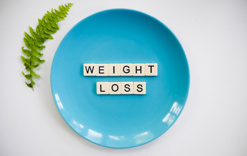 "A blue dinner plate filled with scrabble letter pieces that are arranged to say ""weight loss"""